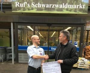 """Scheckübergabe: Marktleiter Gehling überreicht den Scheck über 300 €, Lothar Volkelt von der Tafel sagt """"Dankeschön"""""""